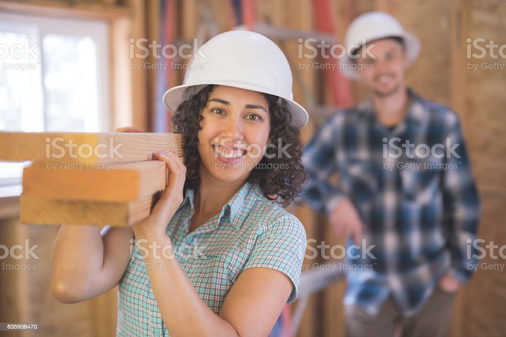 Hispanic female carrying a stack of 2x4's for DIY stock photo