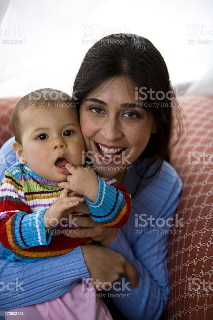 Hispanic female mother hugging baby girl daguther sitting on couch royalty-free stock photo
