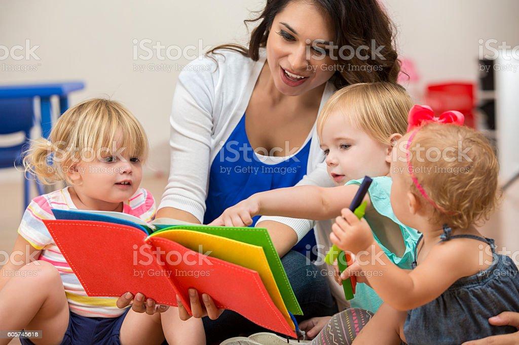 Hispanic female teacher reading a book to cute preschool students stock photo