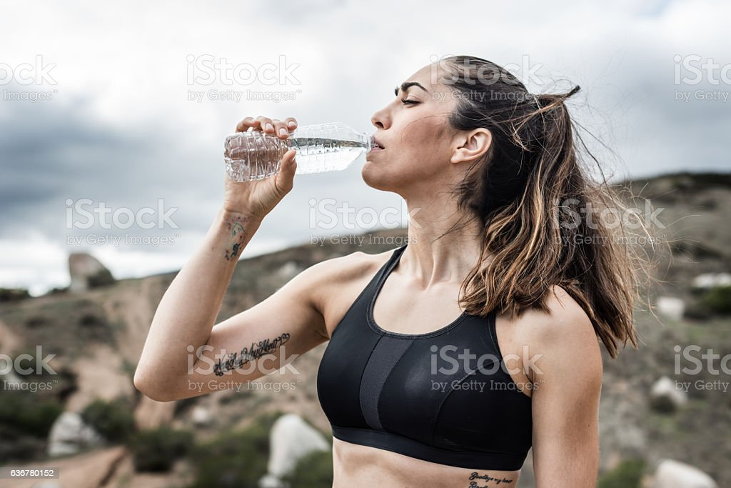 Hispanic Fit Women Resting Drinking Water stock photo