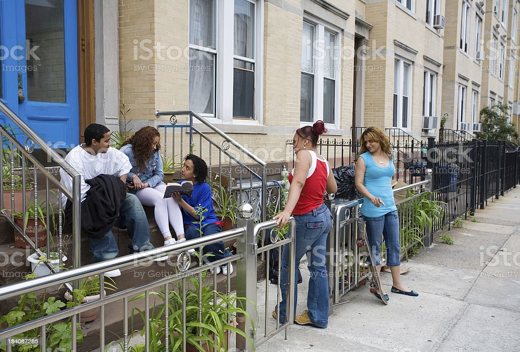 Hispanic friends on steps stock photo