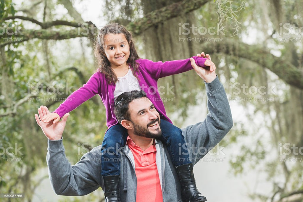 Hispanic girl at park sitting on father's shoulders stock photo