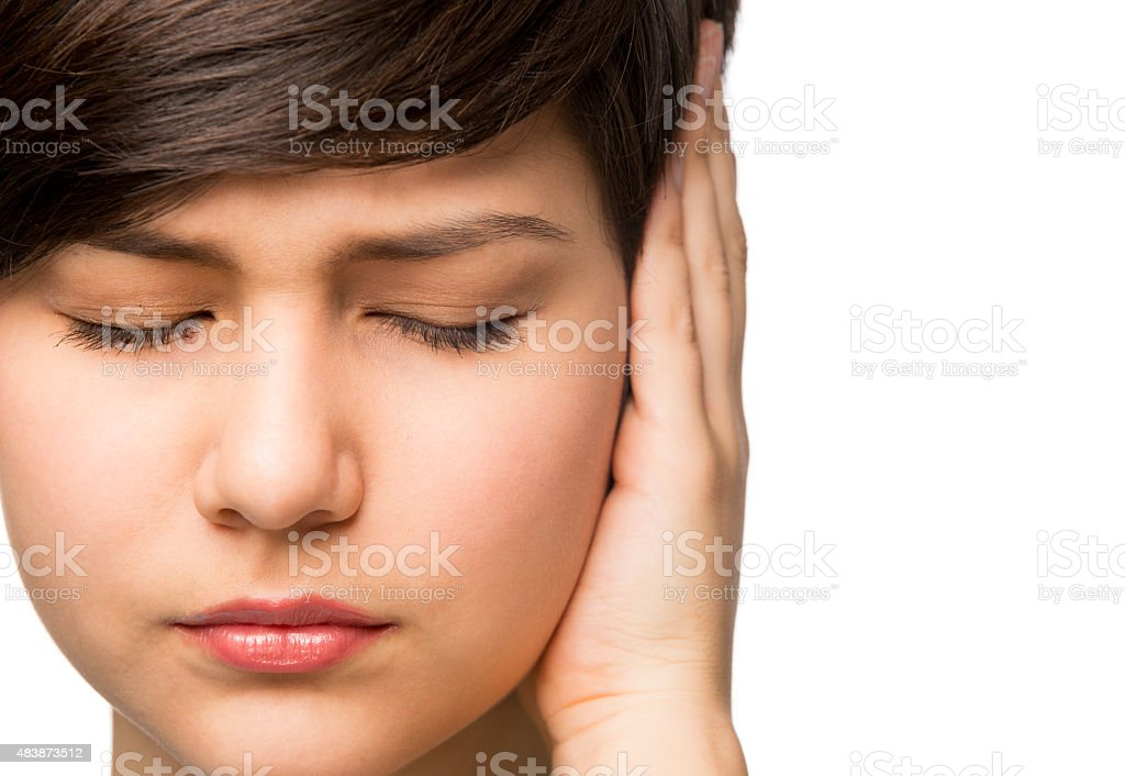Hispanic girl covering her ear with her hand stock photo