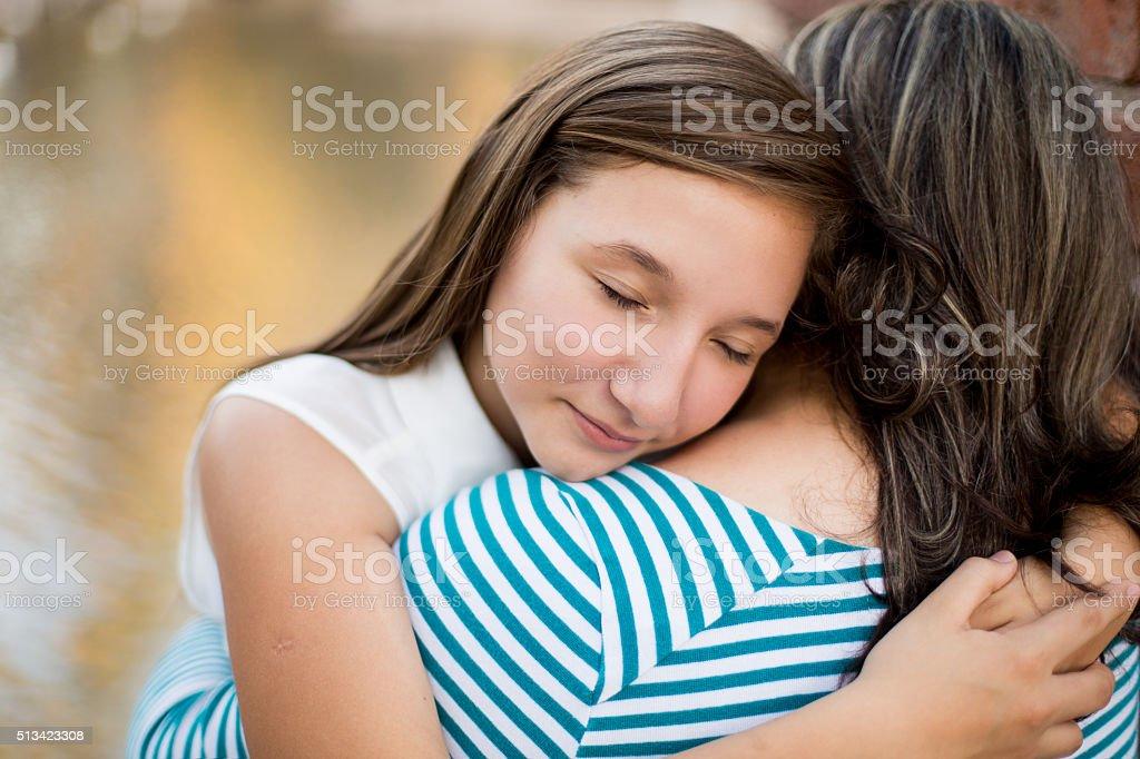 Hispanic girl hugging her mother stock photo