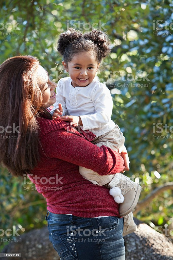 Hispanic girl in mother's arms stock photo