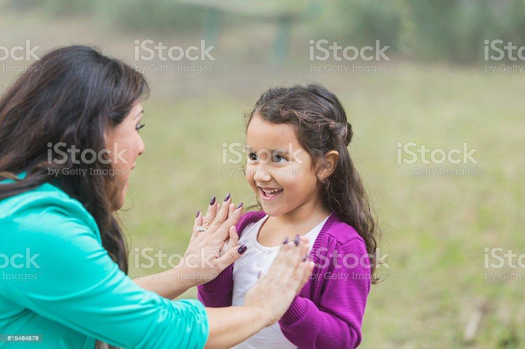 Hispanic girl playing patty cake with mother stock photo