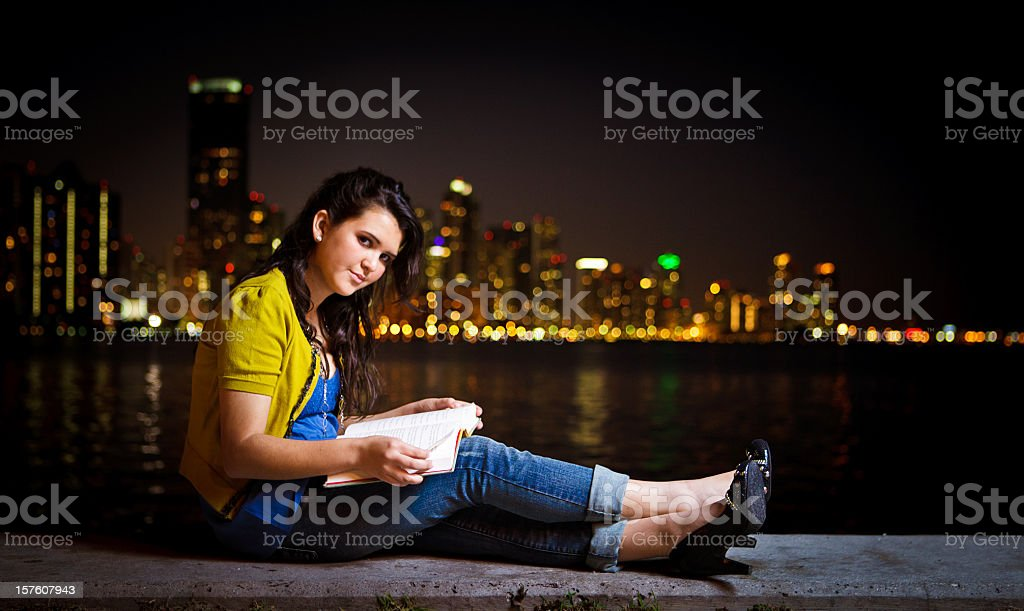 hispanic girl reading a book in front of miami skyline stock photo