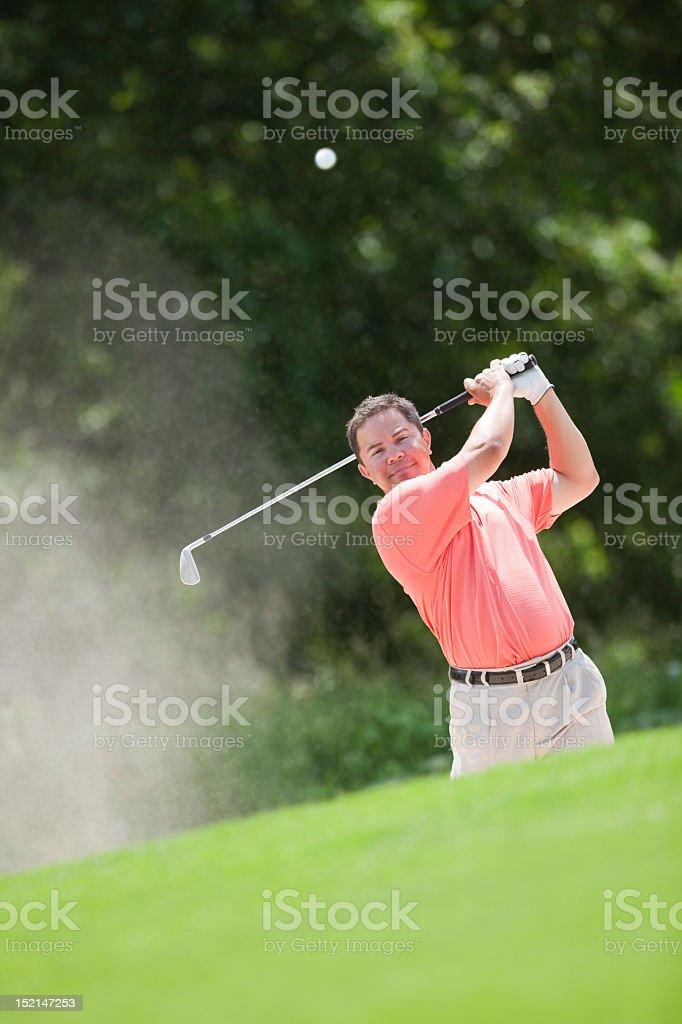Hispanic Golfer Hitting Ball Out of Sand Trap stock photo