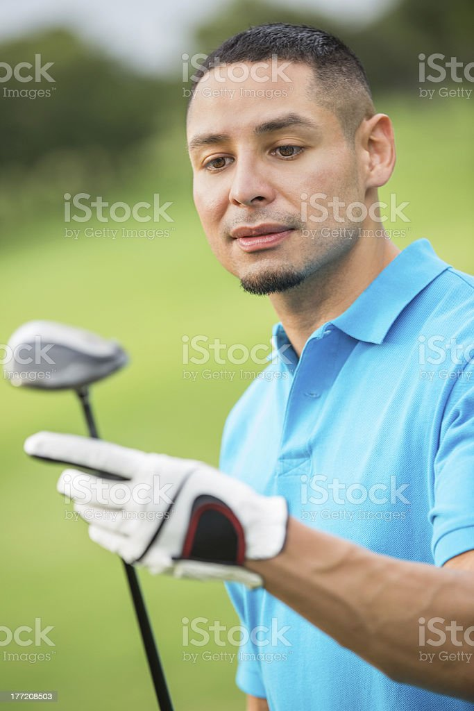 Hispanic golfer looking at club on golf course royalty-free stock photo