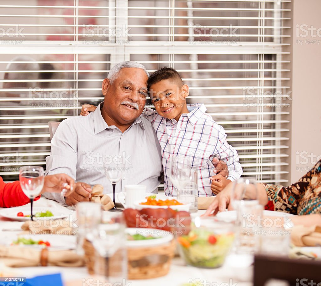 Hispanic grandfather and grandson enjoy family dinner together. Home. stock photo