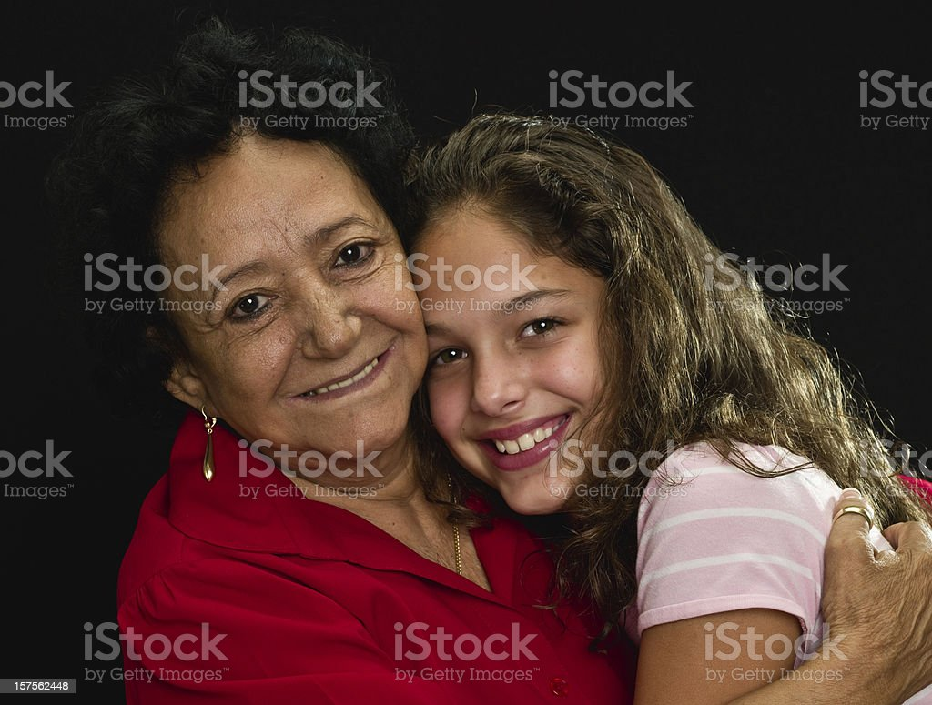 Hispanic grandmother hugging her granddaughter royalty-free stock photo