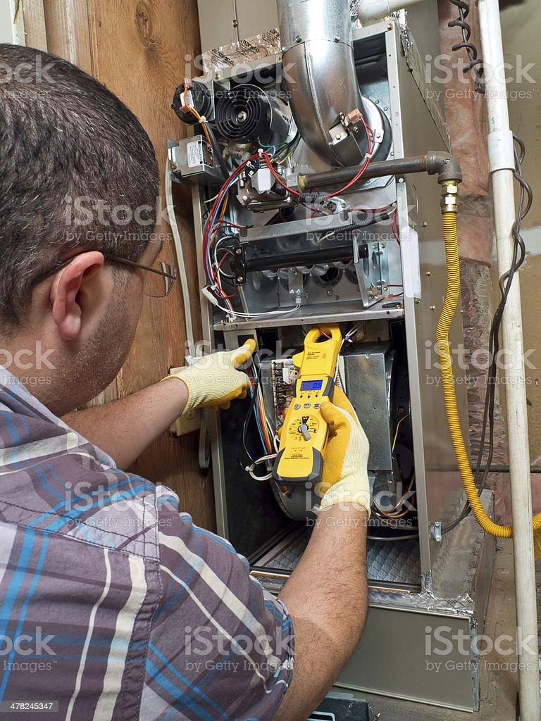 Hispanic handyman repairman conducting residential HVAC repair stock photo