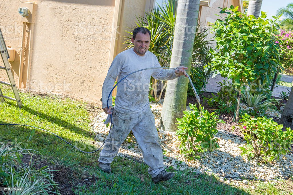 Hispanic house painter walking with paint sprayer at a home stock photo