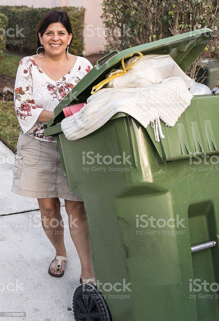 Hispanic Housewife pushing the trash can royalty-free stock photo