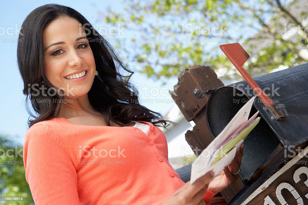Hispanic lady smiling as she checks her mailbox and letters stock photo