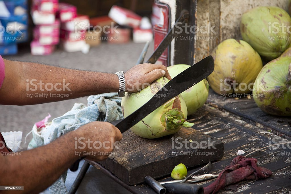 Hispanic Male Cuts Coconut With Machete royalty-free stock photo