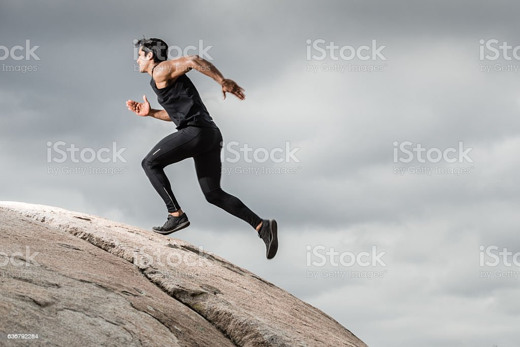 Hispanic Male Running Up A Granite Boulder In The Mountains stock photo