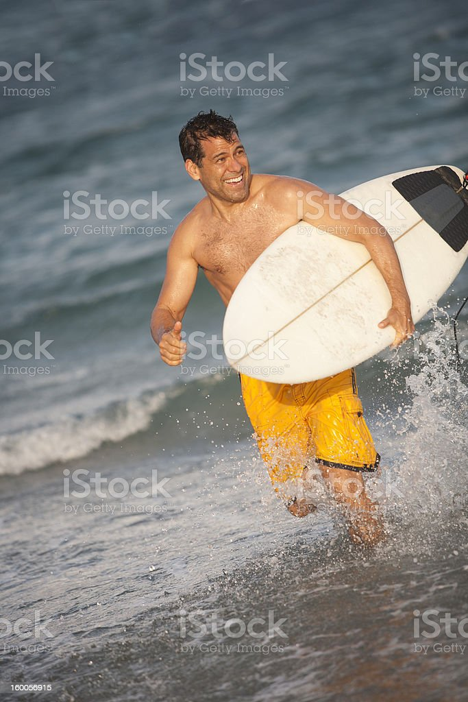 hispanic male with surfboard at the beach running stock photo