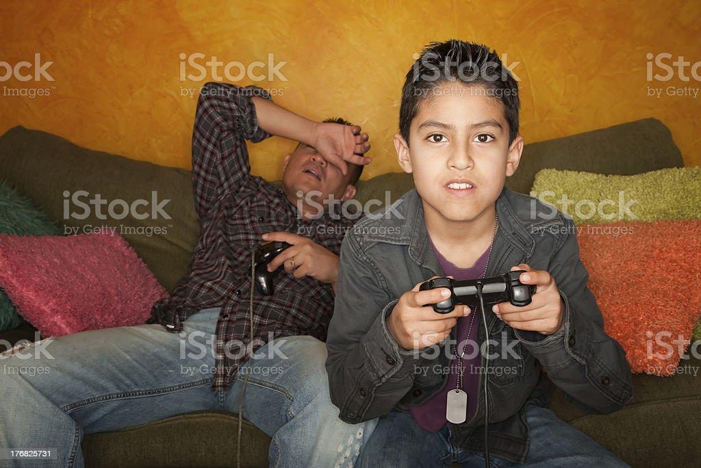 Hispanic Man and Boy Playing Video game royalty-free stock photo