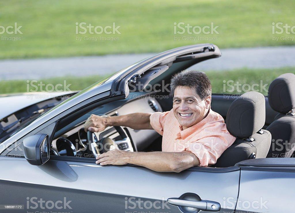 Hispanic man driving convertible stock photo