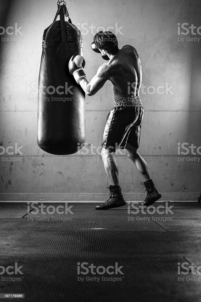 Hispanic Man Hitting a Punching Bag in Black and White stock photo
