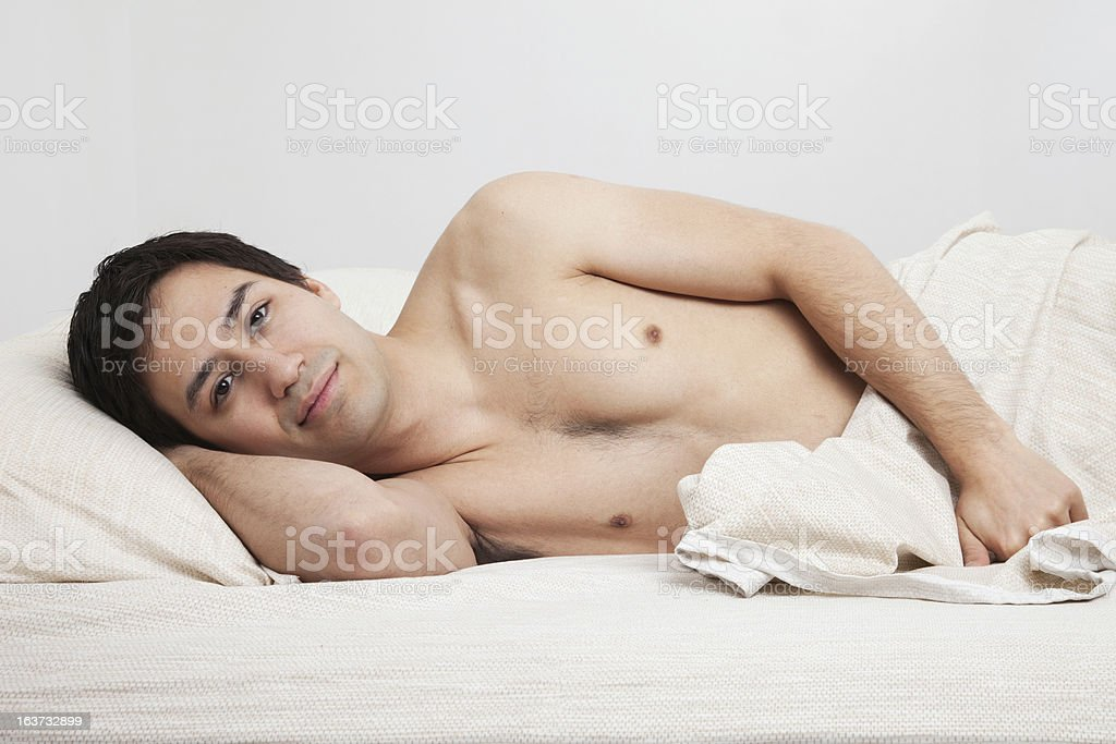 Hispanic man in bed with a soft expression stock photo