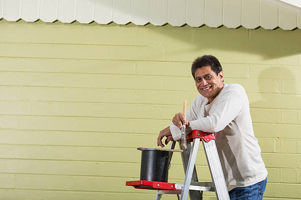 Hispanic Man Painting House Stock Photo - Download Image Now