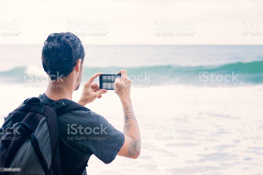 Hispanic Man Photographs Costa Rica Wave on Caribbean Beach Vacation stock photo