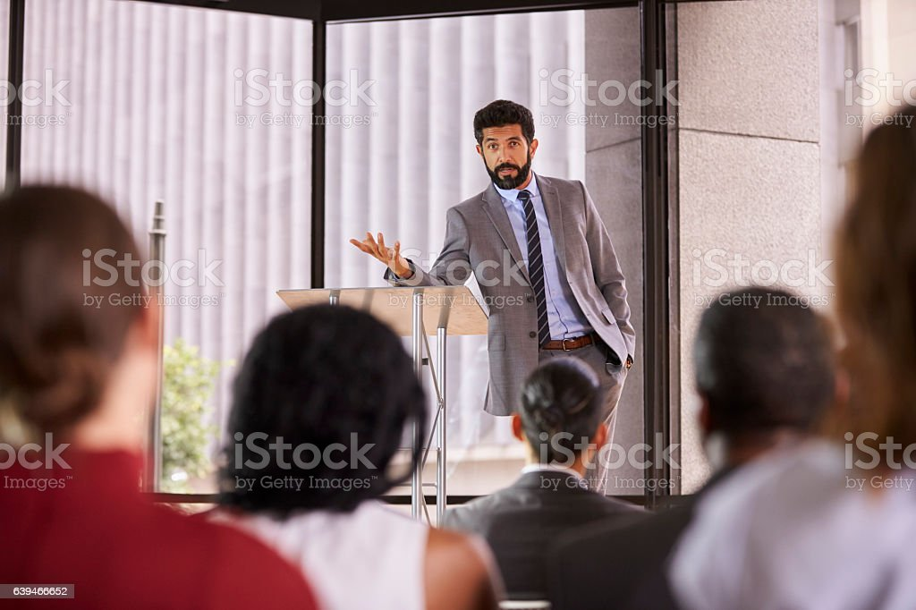 Hispanic man presenting business seminar leaning on lectern stock photo
