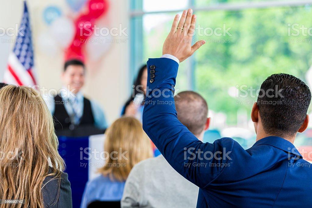 Hispanic man raising hand during political town hall meeting stock photo