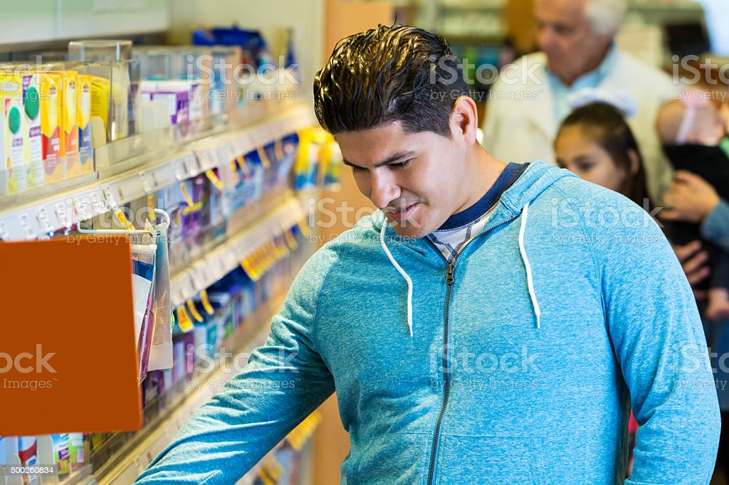 Hispanic man shopping for over the counter medicine in pharmacy stock photo