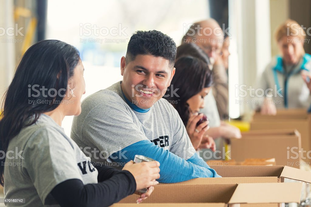 Hispanic man sorting donations in food bank with volunteers stock photo