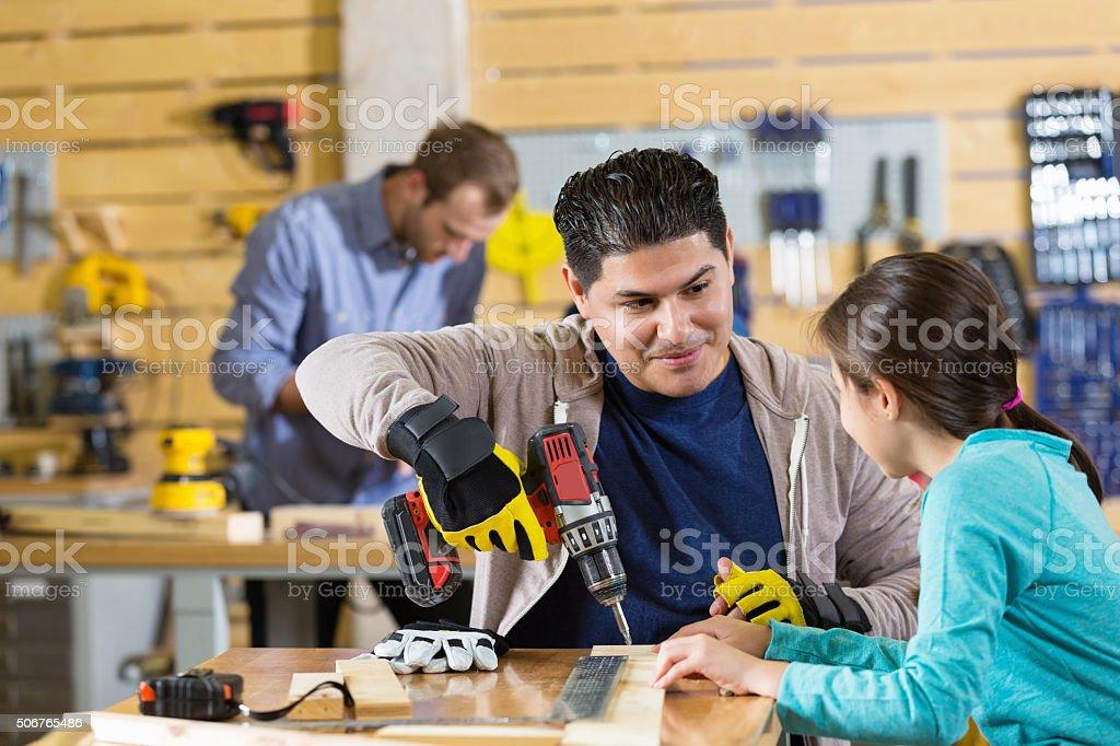 Hispanic man teaching daughter to use power tools in garage stock photo
