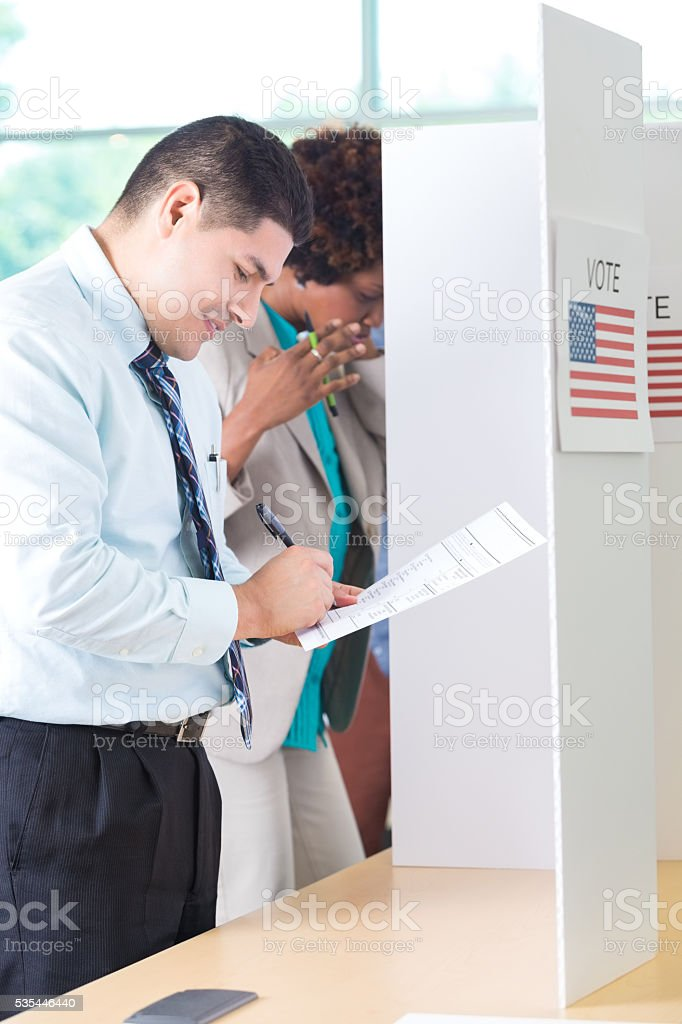 Hispanic Man votes at a voting booth stock photo