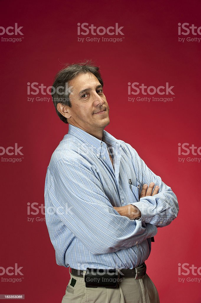 Hispanic man with arms crossed looking at camera against a red background. royalty-free stock photo