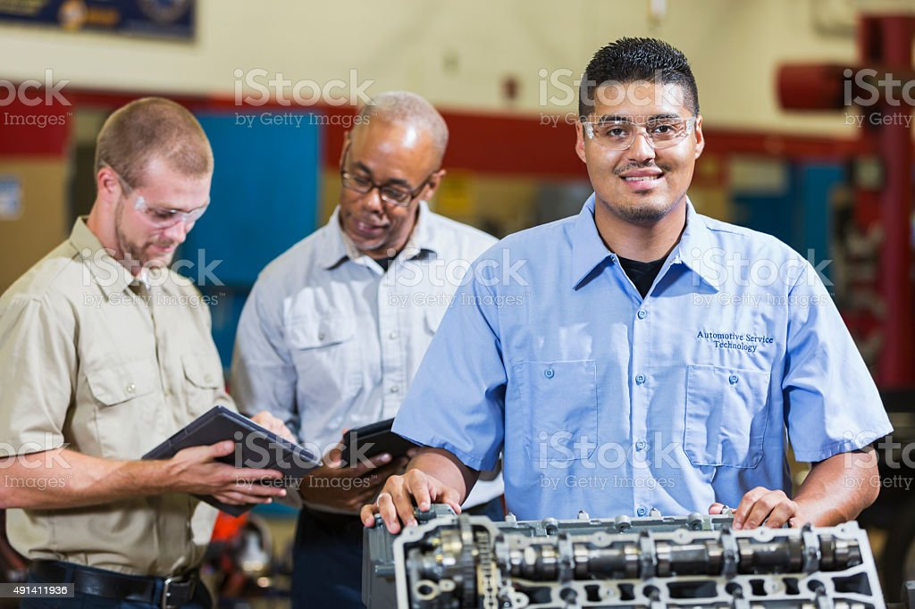 Hispanic man with engine, co-workers on digital tablets stock photo