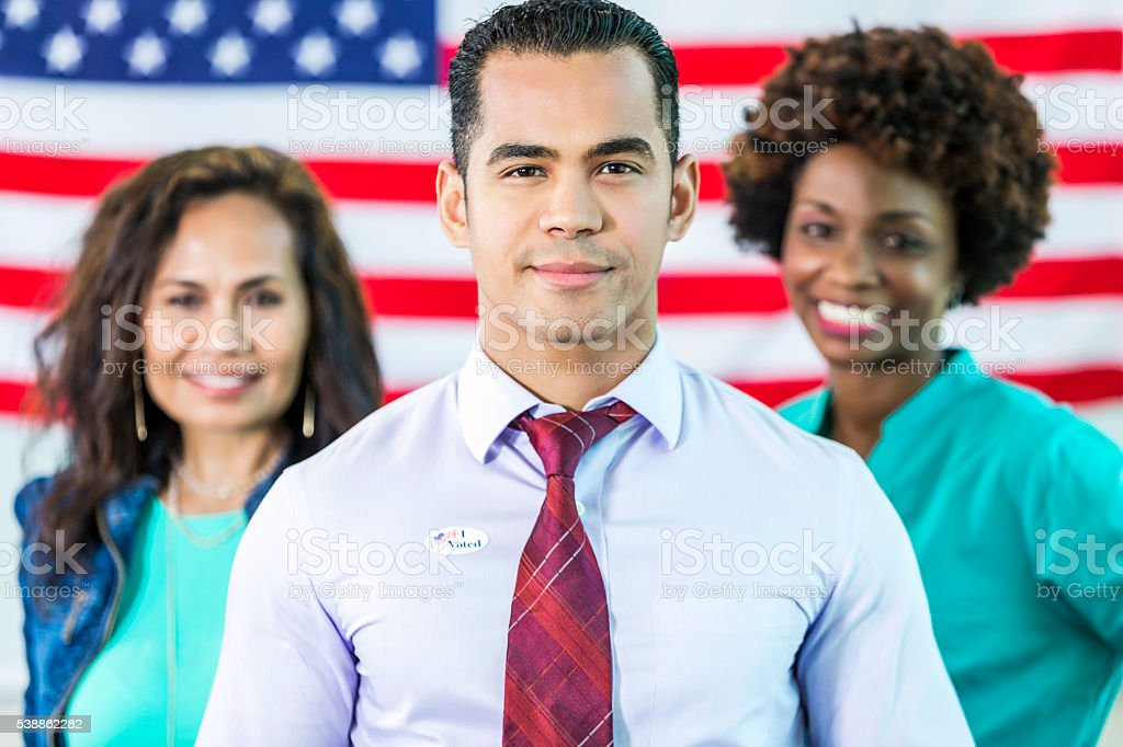 Hispanic Man with team in front of American flag stock photo