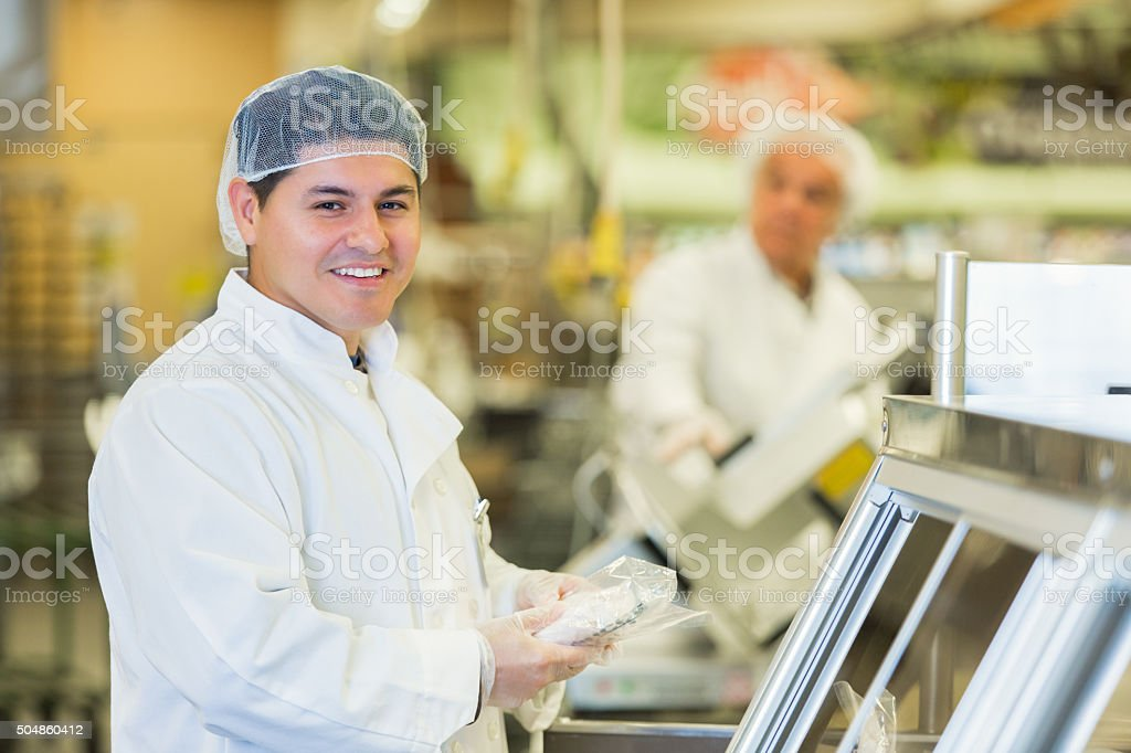 Hispanic man working as butcher or deli manager in supermarket stock photo