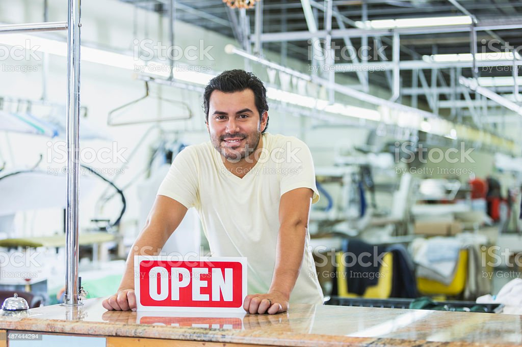Hispanic man working in a dry cleaner with OPEN sign stock photo
