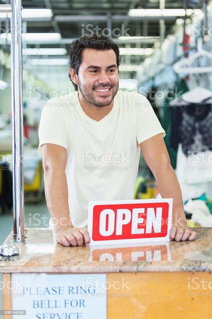 Hispanic man working in dry cleaner with OPEN sign stock photo