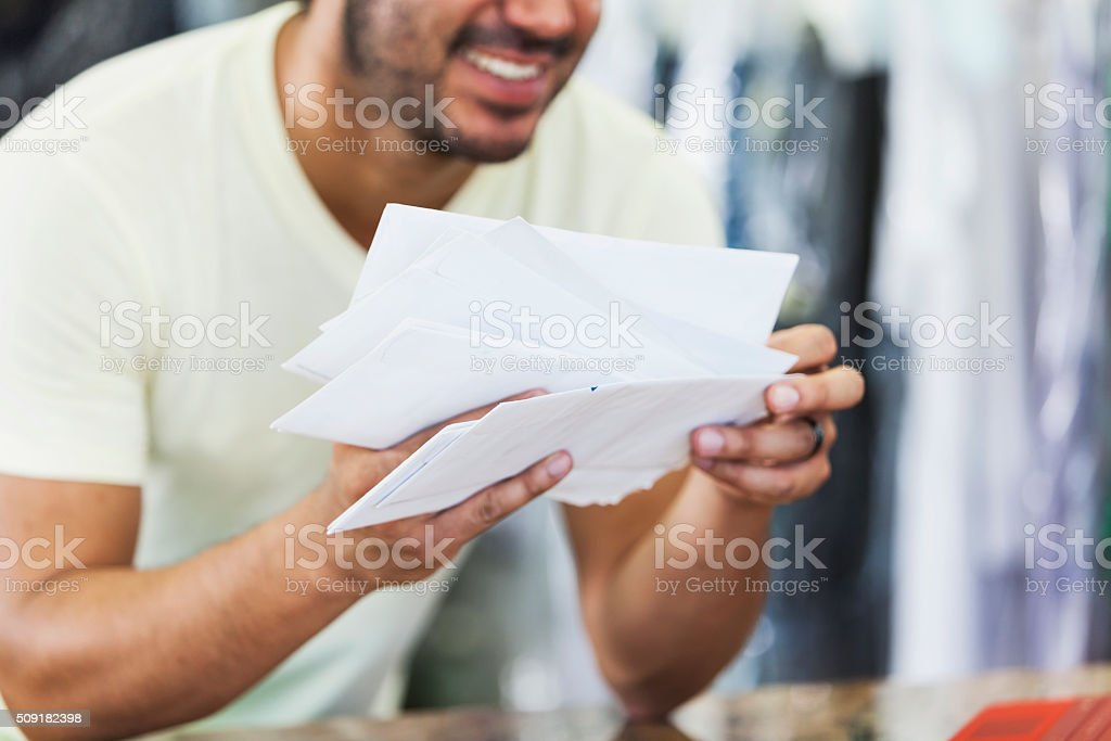 Hispanic man working in dry cleaners opening mail stock photo