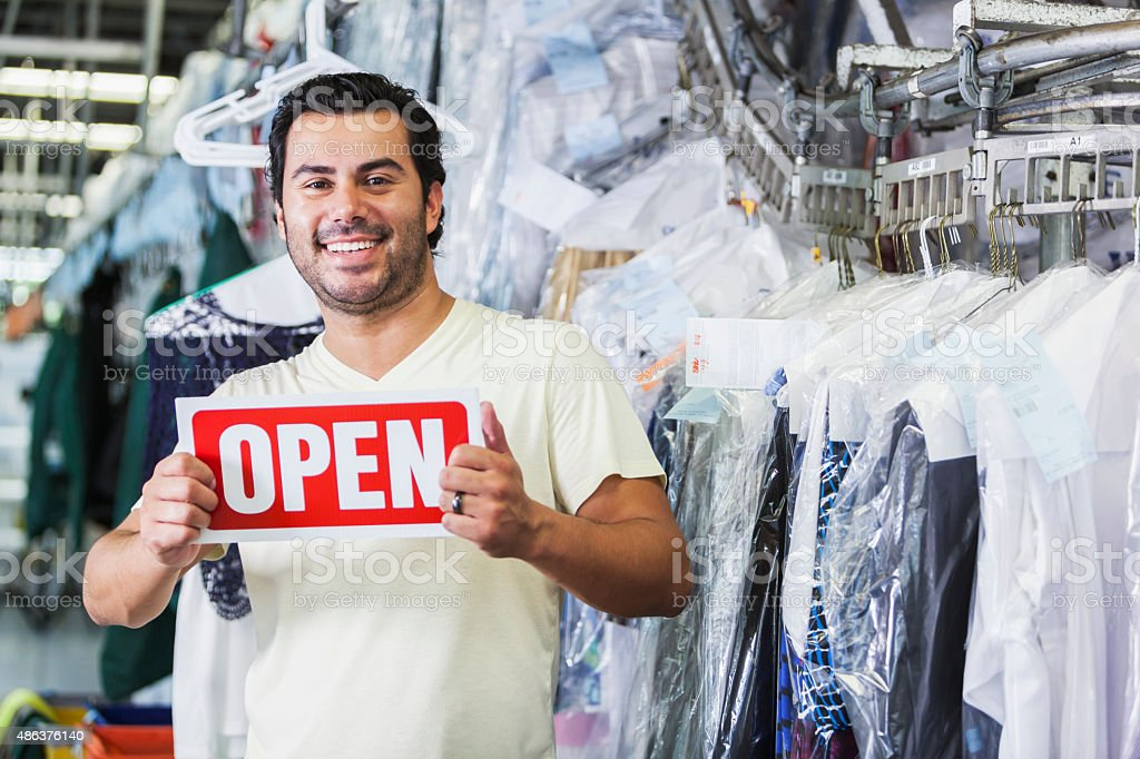 Hispanic man working in dry cleaners with OPEN sign stock photo