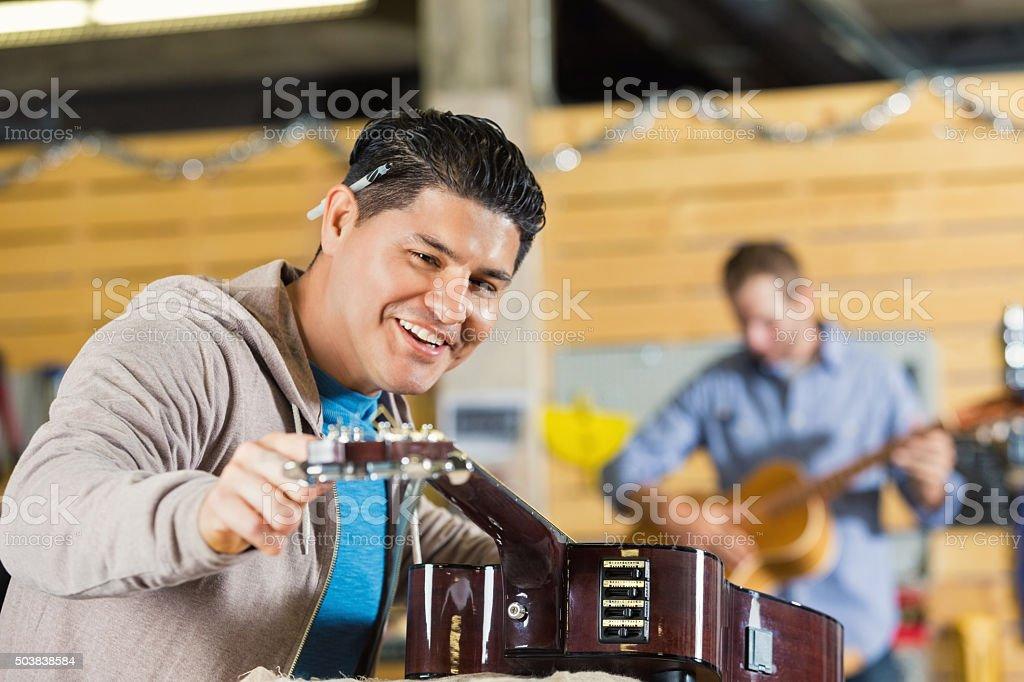 Hispanic man working in musical instrument repair and sales shop stock photo