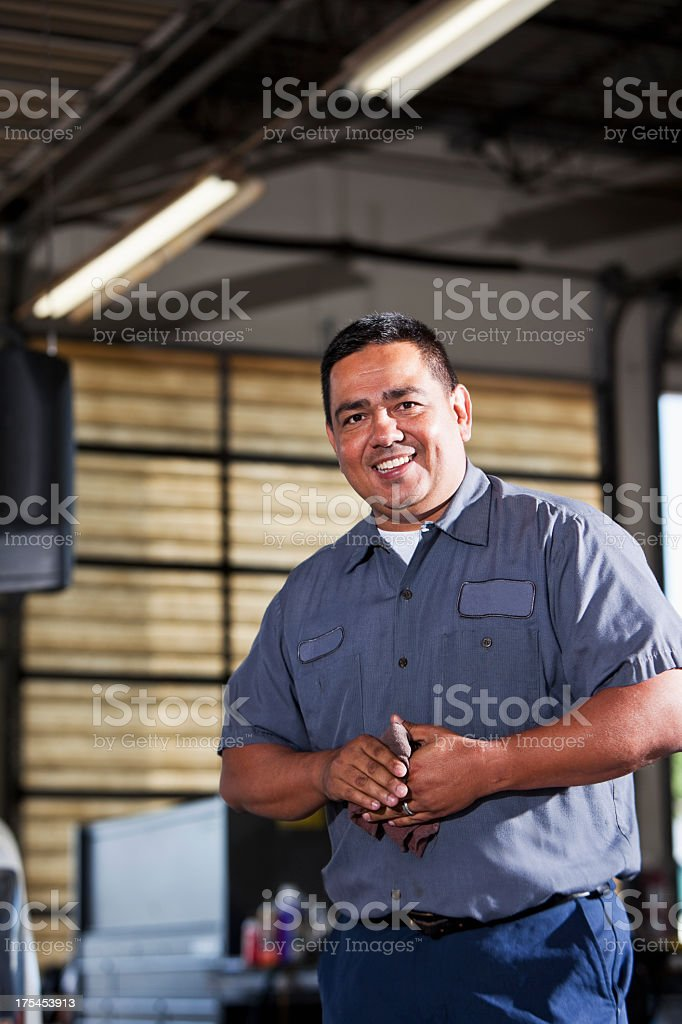 Hispanic mechanic in garage royalty-free stock photo