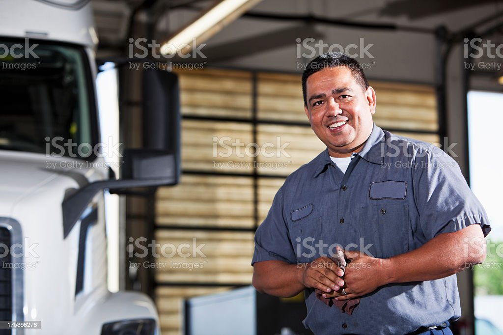 Hispanic mechanic in garage with truck royalty-free stock photo