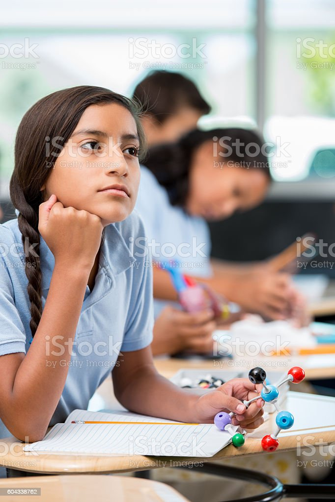 Hispanic middle school student daydreams during science class stock photo