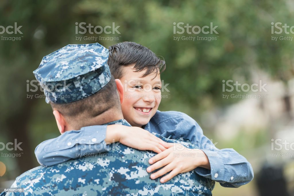Hispanic military man nugging 8 year old son stock photo