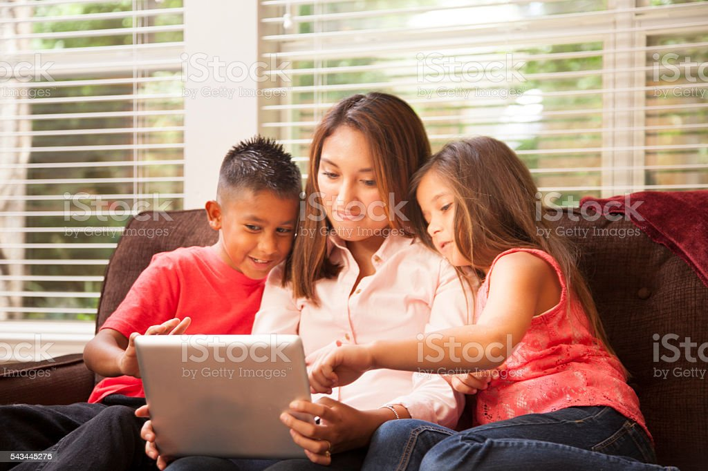 Hispanic mother and children learn on digital tablet at home. stock photo