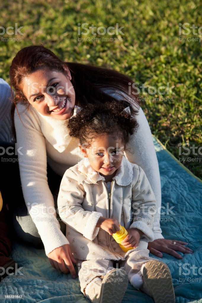 Hispanic mother and little girl at park stock photo