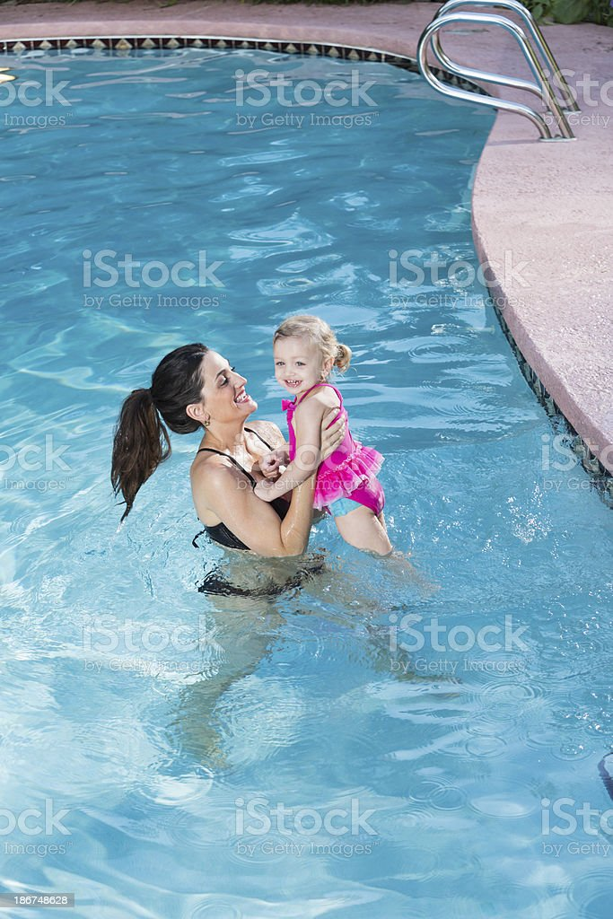 Hispanic mother and little girl in swimming pool royalty-free stock photo